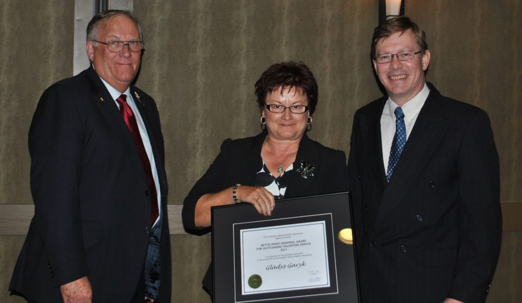 Gladys Garyk of Medicine Hat receiving the Bettie Hewes Memorial Award for Outstanding Volunteer Service. From left to right: Honour Colonel (Ret'd) Donald S. Ethell, Lieutenant Governor of Alberta, Gladys Garyk , David Copus of the Provincial Board.